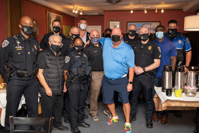 Chris Cognac, the co-founder of Coffee with a Cop, is shown with Clermont police at the Coffee with a Cop event at Cheeser's Palace Cafe in Clermont on Wednesday.