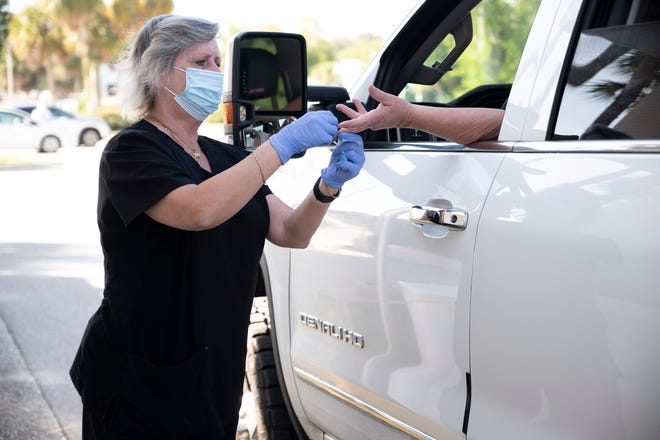 A health care worker conducts a rapid test for COVID-19 at the Lake Square Mall. [Cindy Peterson/Correspondent]