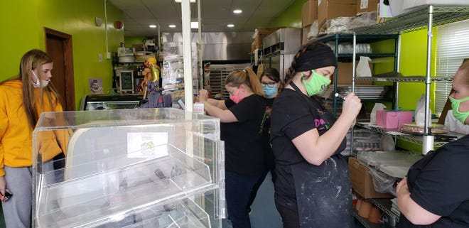 Tara Hupp (right), owner, Pure Love Bakery, looks on as staff helps customers with purchases.