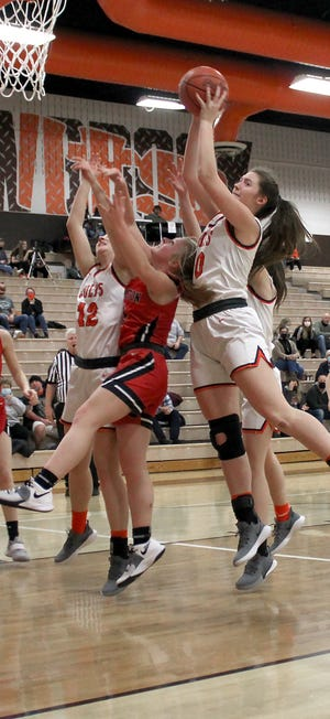 Meadowbrook's Kendyl Cannon (10) goes over a Coshocton player for a contested rebound during Thursday's game at Meadowbrook High School.
