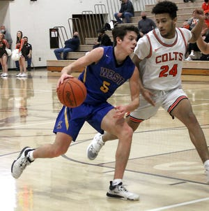 West Muskingum's Kyle Reilly (5) dribbles around Meadowbrook's Malachii Phillips (24) during Thursday's Muskingum Valley League match-up in Byesville. Meadowbrook collected a 74-45 win to capture the MVL Small School Division title with a perfect 9-0 mark.