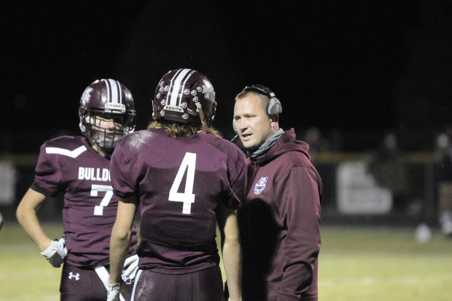 Morenci football coach Ryan Love talks to Jacob Reincke (4) and Rodney Zimmerman during a game in the 2020 season.