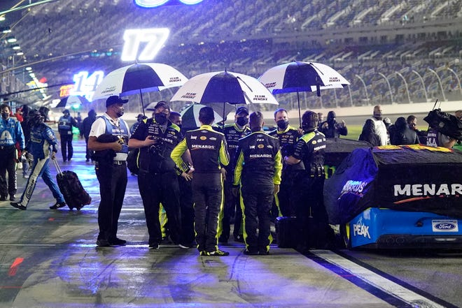 Drivers and crew members seek shelter under umbrellas as rain falls before the second of two qualifying NASCAR auto races for the Daytona 500 at Daytona International Speedway, Thursday, Feb. 11, 2021, in Daytona Beach, Fla.