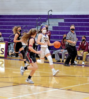 Bronson's Haylie Wilson drives to the bucket in transition past two Charger defenders Thursday night. Wilson led all scorers with 13 points on the night.