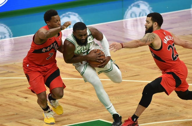 Boston Celtics guard Jaylen Brown (7) splits the defense of Toronto Raptors guard Kyle Lowry, left, and guard Fred VanVleet (23) during the first half of their game Thursday, Feb. 11, 2021, at TD Garden in Boston.