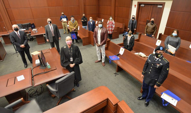 Hailing from nine countries, 10 new U.S. citizens are shown on Friday following a citizenship and naturalization ceremony at U.S. District Court in Erie. Presiding over the ceremony was U.S. District Court Judge Susan Paradise Baxter, near left.
