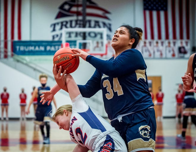 William Chrisman's Jacque David tries to maintain possession as she gets tangled with Truman defender Erynn Boatright in Thursday's game at Truman. David scored 11 of her 17 points in the fourth quarter to help the Bears stave off a challenge from the rival Patriots and claim a 44-33 win.