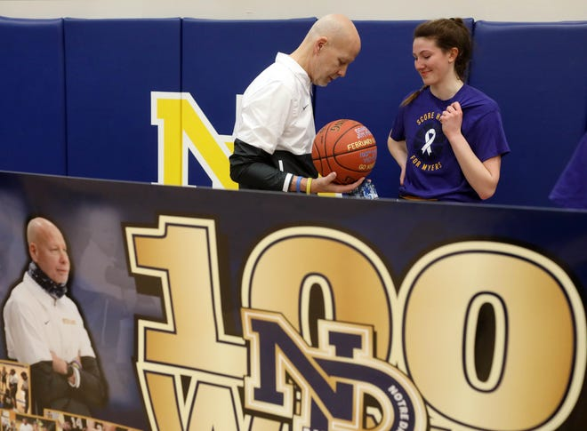 Notre Dame High School's head coach Jim Myers and Gabby Deery (12) look at the basketball he was presented with following his 100th career victory with the team's win over New London High School, Thursday Feb. 11, 2021 at Notre Dame's Father Minett Gymnasium.