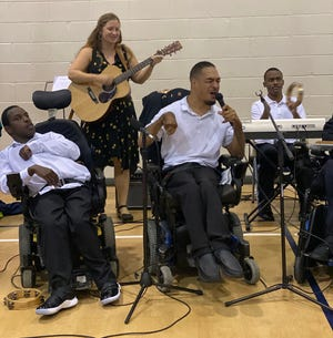 The Flashbacks special-needs pops band, led by Music Director Abigal Gruber (rear), perform for fellow clients at the Pine Castle center for adults with intellectual and developmental differences.