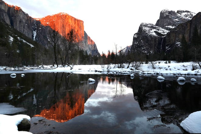 El Capitan is reflected in the Merced River at sunset on Feb. 1, 2021, as California's Yosemite National Park reopens after being closed since Jan. 19, 2021, when a storm caused hazardous snow and wind conditions.