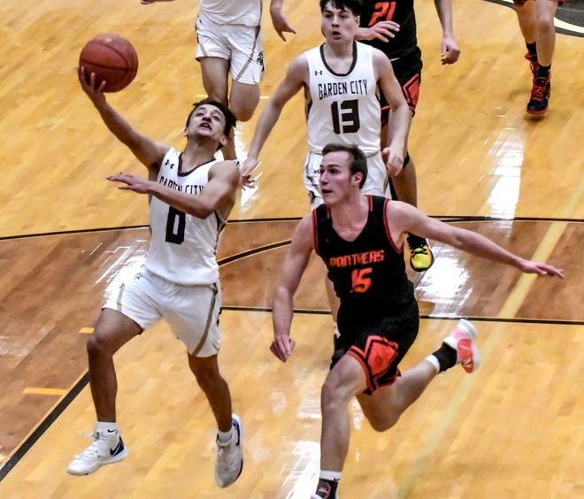 Garden City High School's Isaac Flores, left, goes up for a basket past Great Bend's Cal Dunekack off a fast break Thursday at GCHS.  Flores was the high scorer in the game with 15 points, as the Buffaloes defeated the Panthers, 58-38.