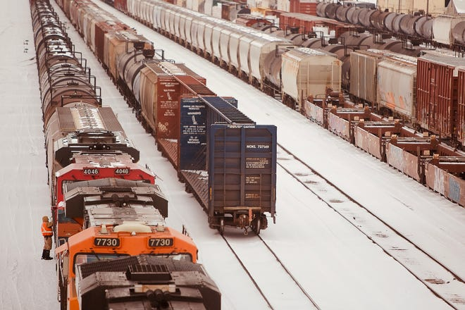 A BNSF Railway employee inspects a train car in the bitter cold at the company's freight yard south of Galesburg on Friday, Feb. 12, 2021.