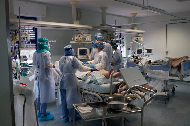 Nurses and doctors tend to a patient in a COVID-19 Intensive Care Unit at the Curry Cabral hospital in Lisbon, Thursday, Feb. 11, 2021. A January surge of cases in Portugal has ebbed amid a lockdown, but deaths and pressure on hospitals remain high. (AP Photo/Armando Franca)