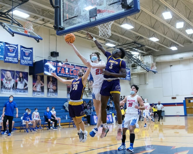 West Henderson's Nick Pate goes up for a layup between North Henderson defenders Zachriah McDaniel (3) and Evan Simpson on Thursday night at West.