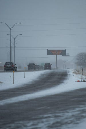 Road signs warn drivers about road conditions as snow accumulates on Friday, Feb. 2, 2021, in Lubbock, Texas.