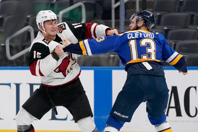 Arizona Coyotes' John Hayden (15) and St. Louis Blues' Kyle Clifford (13) fight during the first period of an NHL hockey game Monday, Feb. 8, 2021, in St. Louis.