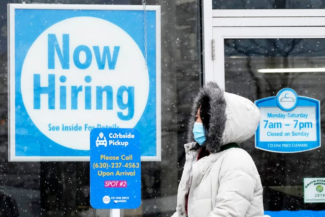 "FILE - In this Feb. 6, 2021 file photo, a woman walks past a ""Now Hiring"" sign displayed at a CD One Price Cleaners in Schaumburg, Ill. (AP Photo/Nam Y. Huh, File)"