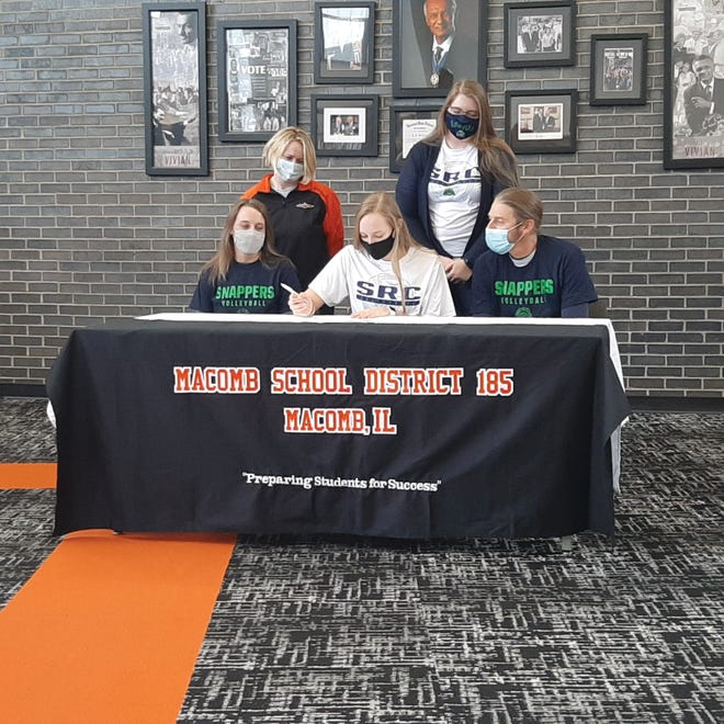 Lael McKee (center) signs with Spoon River College as family and coaches watch.