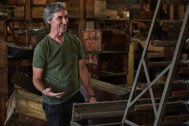 """Mike Wolfe of the American Pickers television show, goes through a building full of """"stuff"""" in an episode from the show."""