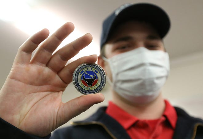 Ryan Hart, an Exeter firefighter serving in the Air National Guard, holds the Commander's Coin he was presented Friday for his exemplary service in the Middle East and being on the frontlines of COVID-19.