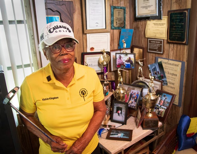 Victoria Kingdom, 92, poses with some of the many golf awards and trophies she has at her home in Riviera Beach.