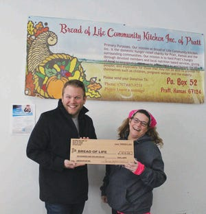 Kyle Irvin and Tonja Harrison laugh over an extra-large wooden check that represented $610 donated to the Bread of Life Kitchen. Irvin ogranizes meal every Tuesday at the food service outlet, 309 S Main, Pratt.