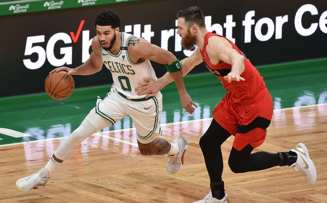 Feb 11, 2021; Boston, Massachusetts, USA; Boston Celtics forward Jayson Tatum (0) drives to the basket wile Toronto Raptors center Aron Baynes (46) defends during the first half at TD Garden. Mandatory Credit: Bob DeChiara-USA TODAY Sports