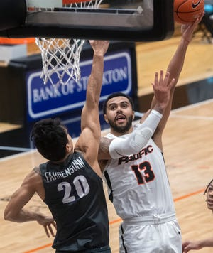 Pacific's Jeremiah Bailey, right, hooks the ball over Portland's Takiula Fahrensohn during a WCC men's basketball game at Pacific's Spanos Center in Stockton.