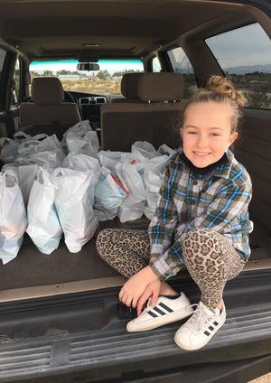 Olivia Freiberg, 8, sits with bags of hygiene products that she purchased using half of her savings and some of the stimulus money that her parents received due to the pandemic. In total, she helped 50 people with her donation.