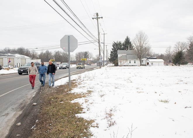 Rakesh Patel, owner of a planned gas station to be built on the Deerfield Circle, walks with Deerfield Trustee Mark Bann along Route 224 toward the Deerfield Circle.