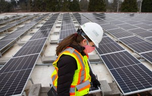 City of Eugene project manager Shauna Parker walks past a solar array on the roof of the Echo Hollow Pool building that is part of an upgrade to the facility with the goal of reducing carbon emissions for the city as a whole.