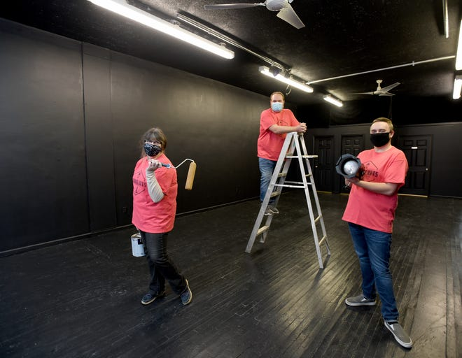 Linda Radek, David Lee (center) and Jared Sparks prepare Avenue Arts' new theater location in downtown Canton.