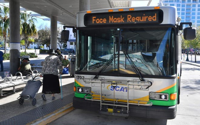 To try to slow the spread of COVID-19, the federal government has issued an order requiring everyone on public transit systems and in transit stations to wear face coverings. A sign on the front of a SCAT bus at the downtown Sarasota transfer station reminds riders about the new rule.