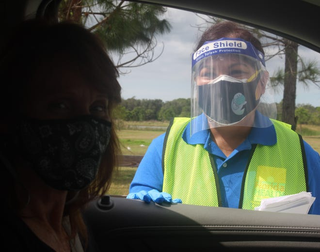 """Manatee County health official Runa Badal greets clients at a drive-thru COVID-19 vaccination operation Feb. 12 at Tom Bennett Park in Bradenton. Vaccination is an important part of the effort to reach """"herd immunity"""" against the virus, but not the only contributing element."""
