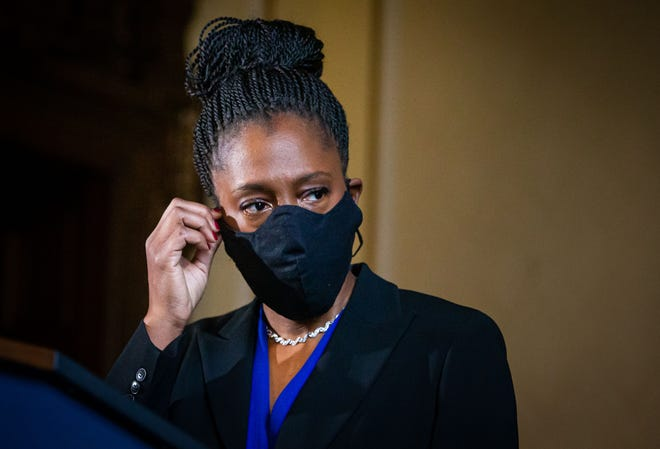 Dr. Ngozi Ezike, director of the Illinois Department of Public Health, removes her face mask to give an update on the COVID-19 pandemic in Illinois during a press conference at the state Capitol on Jan. 11.