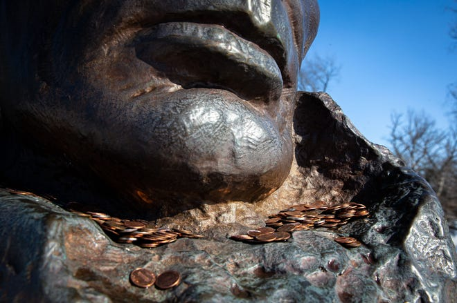 A tradition of leaving pennies at the statue of Abraham Lincoln--the 16th president--goes along with rubbing his nose for good luck at the Lincoln Tomb State Historic Site in Oak Ridge Cemetery in Springfield, Ill., Friday, February 12, 2021.