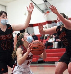 Trinity Hostetler of Howardsville Christian eyes the hoop around Marcellus defenders in prep basketball action on Thursday.