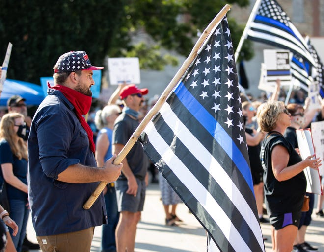"Will Pope holds a thin blue flag while attending an Aug. 25 ""Back the Blue"" rally in front of the Topeka Performing Arts Center. Pope was arrested last week in connection with seven federal crimes linked to a Jan. 6 riot at the nation's Capitol in Washington, D.C."