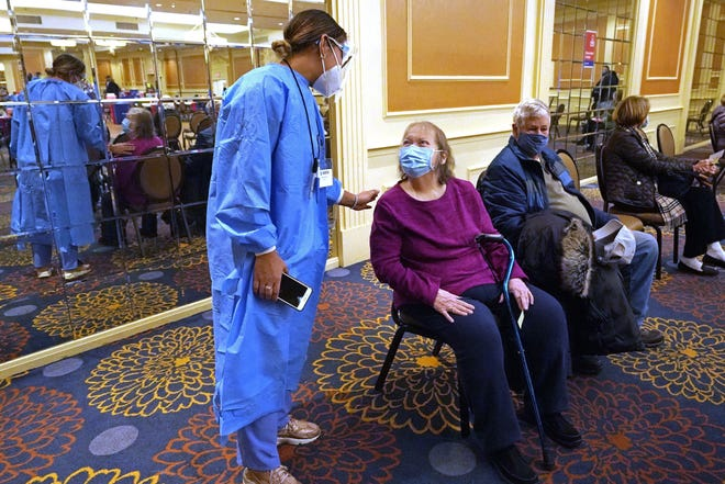 Nurse Maria Agramonte makes sure Audrey Lermond is feeling okay as she sits with her husband, Bob, in the observation area after she received a COVID-19 vaccination at the Doubletree Hotel, Friday, Feb. 5, 2021, in Danvers, Mass. (AP Photo/Elise Amendola)