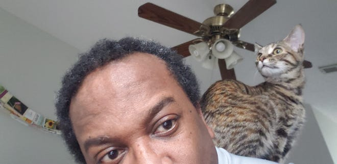 Rosie finds a comfortable spot on the back of fayobserver.com's Myron B. Pitts.