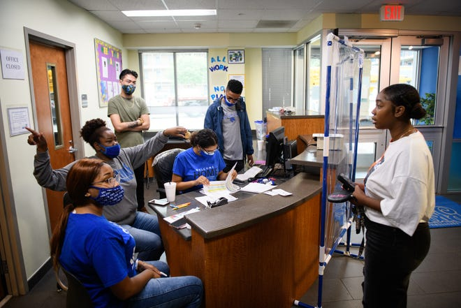 Student Kim Mitchell, right, checks in with the front desk before heading up to her dorm room at Fayetteville State University on July 30.