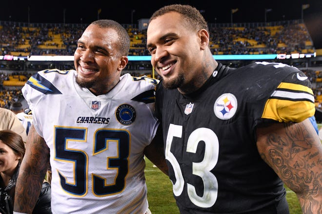 Pittsburgh Steelers center Maurkice Pouncey, right, and his brother, Los Angeles Chargers center Mike Pouncey pose after playing against each other in a game in Pittsburgh. The twin brothers announced their retirement from professional football Friday.
