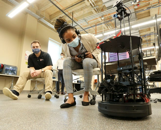 The University of Alabama demonstrated an early prototype of a communications robot designed to aid police officers Friday, Feb. 12, 2021. Altoniece Williams, from Tuscaloosa Police Department, inspects the robot as she operates the controls while UA engineering student Glen Merritt stands by to give her instructions should she need any help. [Staff Photo/Gary Cosby Jr.]
