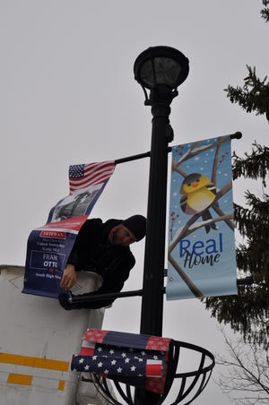 Andy Beare, the urban forester for Hilliard, places the first banners of Hilliard's for Hometown Heroes program Feb. 12 on Main Street in Old Hilliard. Beare worked with the city's service department to replace winter-themed banners with the Hometown Heroes banners on each light pole throughout Old Hilliard.