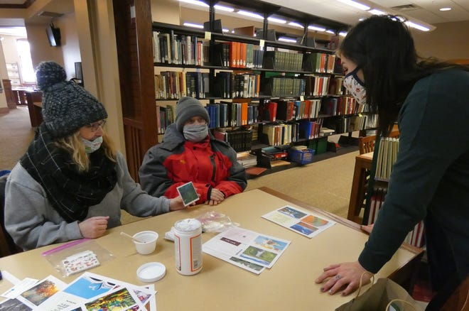 Jill Burling of RNI, Inc., and her client, Robbie Forster, show his coaster craft to Erin Rhoades Thursday morning at the Bucyrus Public Library.