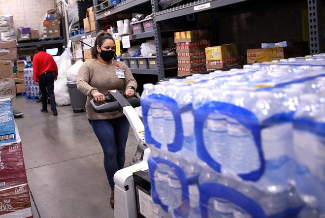 Amber Campos moves a pallet of bottled water from a semi-trailer truck at the loading dock of the H-E-B grocery store at in San Angelo on Tuesday. Many residents have been unable to use water from their faucets for days due to contamination.