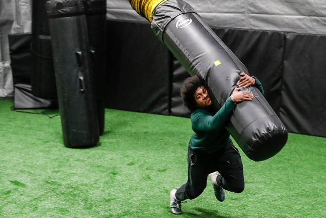 Former Michigan State linebacker Antjuan Simmons tackles a bag during a full speed tackling simulation workout at the Elite Tackling Academy in Grand Blanc, Mich., Wednesday, Feb. 10, 2021.
