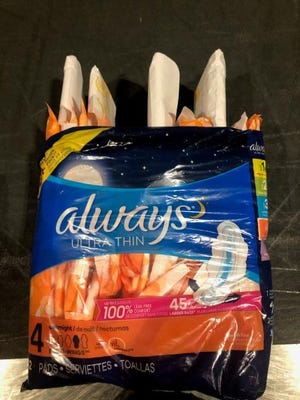 Money was concealed in a sanitary napkins package, U.S. Customs officers said.