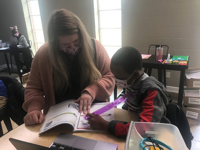 Mabel Sowell, a Salvation Army employee, helps Quentin Catson with his school work on Wednesday.