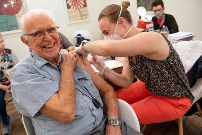 A nursing home resident is all smiles as he receives a COVID-19 vaccine.